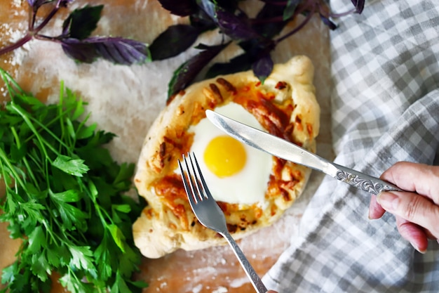 Khachapuri with fork and knife.