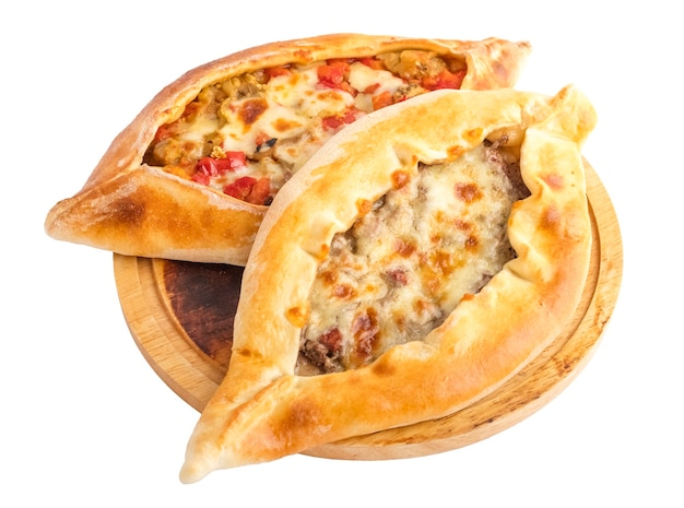Khachapuri with vegetables and khachapuri with meat filling on a round wooden tray