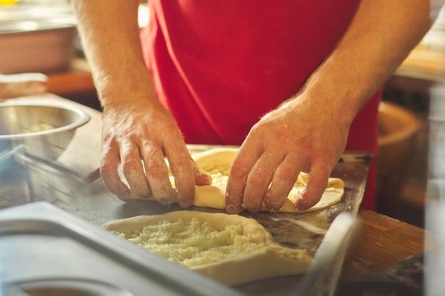 焼きたてのパン、伝統的なグルジア料理のトップビューでkhachapuriを準備する料理人の手