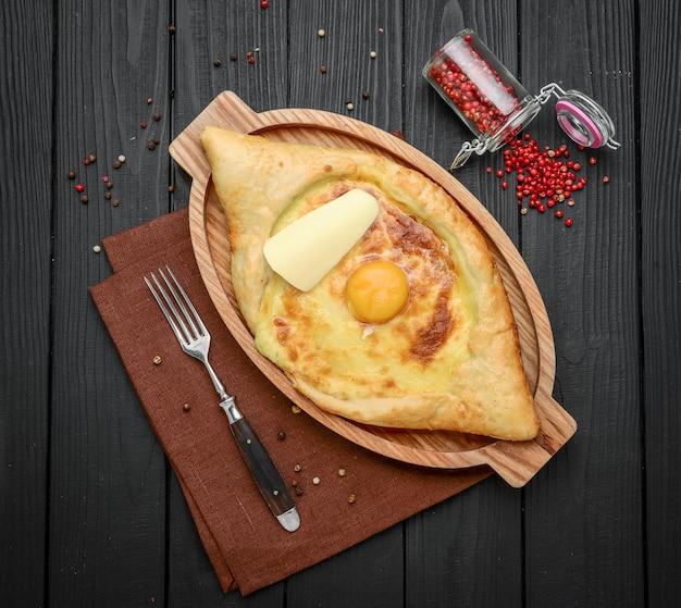 レストランでフォークとアジャリアンkhachapuriの成分を混合する手。チーズと卵黄が入ったオープンパンパイ。おいしいグルジア料理。