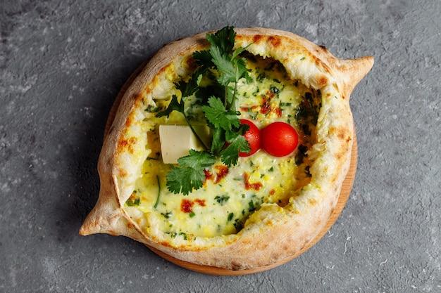アジャリアンkhachapuri、チーズ、ほうれん草、トマト、ハーブ。グレーブルーのボードでジョージア料理。フラット横たわっていた。上面図