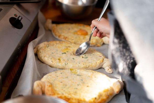料理のマスタークラス。 khachapuriを準備する人々の手のクローズアップ。伝統的なジョージアンチーズのパン。グルジア料理。認識できない大きな家族の調理手をクローズアップ