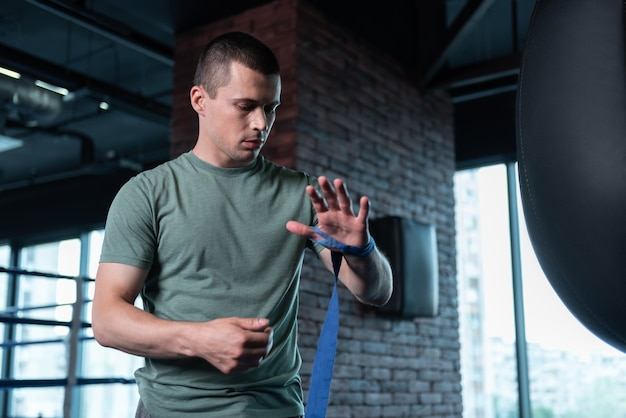 Khaki shirt. dark-haired skillful sportsman wearing khaki shirt training hard in gym before participating in competition