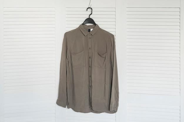 Рубашка цвета хаки висит на вешалке. белый деревянный экран. модный гардероб