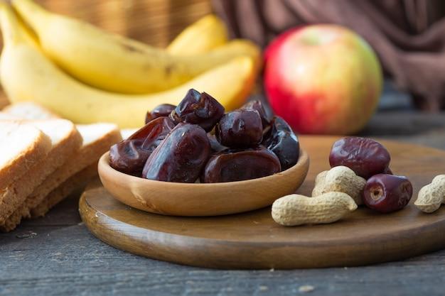 側面図の木製バスケットにカラスナツメヤシ。木のテーブルにコピースペースを持つ日付フルーツ。ナツメヤシの実は、ラマダンやメジョルの食べ物です。