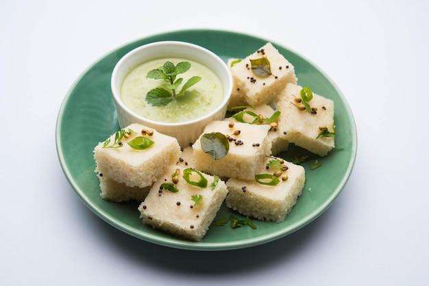 ご飯またはウラドダルでできたカマンホワイトドクラは、インドのグジャラート州で人気の朝食またはスナックのレシピで、グリーンチャツネとホットティーを添えています。セレクティブフォーカス