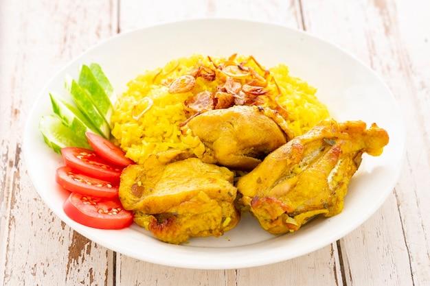 Као мок гай, тайская мусульманская версия индийского бирьяни, ароматный желтый рис с курицей в белой керамической тарелке на белом фоне текстуры старого дерева, курица бирьяни, бириани, бериани