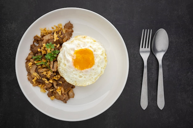 Khao moo tod kratiam kai dao, thai food, streamed rice topped with fried pork with garlic and fried egg in ceramic plate beside fork and spoon on dark tone texture background