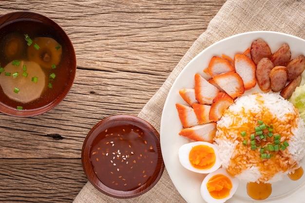 Кхао му даенг, кхао му данг, тайская кухня, струйный рис с красной жареной свининой, подача со сладким соусом, яйцом, китайской колбасой, огурцом, супом из свиной кости, редисом и грибами шиитаке, чар сиу