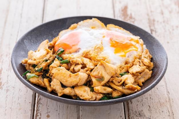 Као пад ка прао гай кай дао, тайская еда, струйный рис, покрытый базиликом, жареный цыпленок и яичница в черной керамической тарелке на белом фоне текстуры старого дерева
