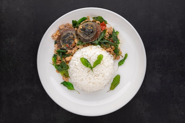 Khao pad ka prao kai yeow ma, thai food, streamed rice with basil stir fried century egg and mince pork in ceramic plate on dark tone texture background, top view