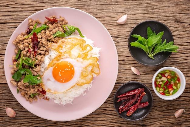 카오 팟 카 프라오 무 섭 카이 다오(khao pad ka prao moo sub kai dao), 태국 음식, 바질 볶음 돼지고기, 생선 소스 옆에 튀긴 계란, 바질 잎, 마른 칠리, 마늘을 소박한 나무 배경에 얹은 스트리밍 쌀, 꼭대기 전망