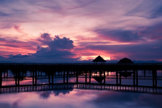 日没時に美しい空を持つ橋のシルエット、khao sam roi yot国立公園、タイで日没時の蓮の湖