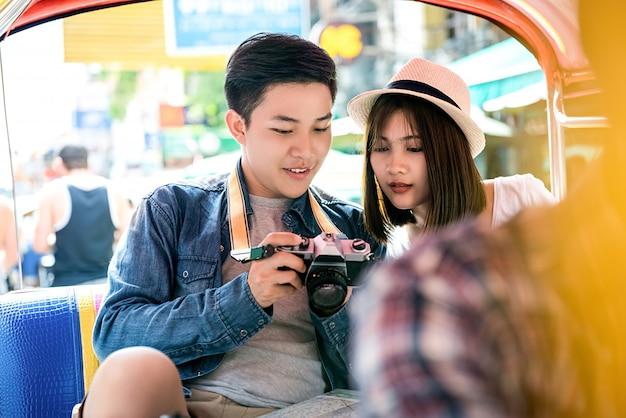 Молодые азиатские туристы пары путешествуя на местном такси тук-тук в дороге khao san, бангкоке, таиланде