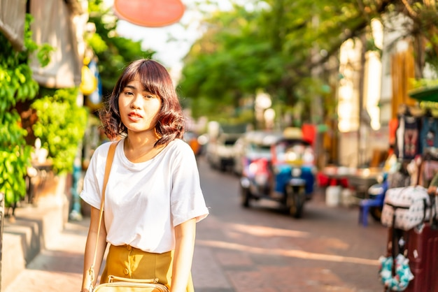 Счастливая и красивая азиатская женщина путешествуя на khao sarn road, таиланде