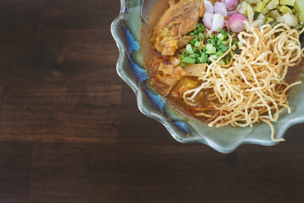 Khaosoi, thai curry noddle soup with chicken, northern style on the wooden table