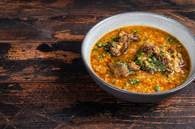 그릇에 쌀, 토마토, 향신료를 넣은 kharcho 쇠고기 고기 수프. 어두운 나무 배경입니다. 평면도. 공간을 복사합니다.