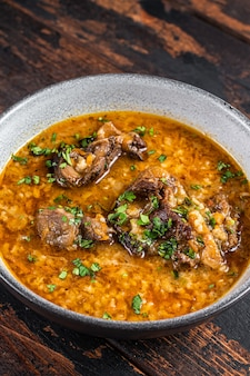 그릇에 쌀, 토마토, 향신료를 넣은 kharcho 쇠고기 고기 수프. 어두운 나무 배경입니다. 평면도.