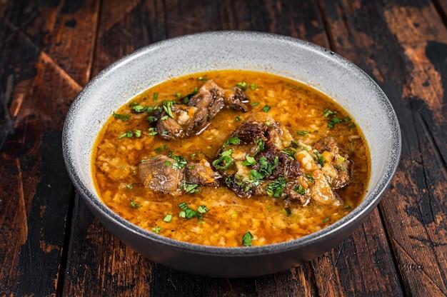 Суп харчо из говядины с рисом, помидорами и специями в миске. темное дерево