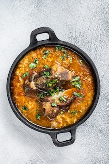 Суп харчо с говядиной, рисом, помидорами и специями на сковороде. белый