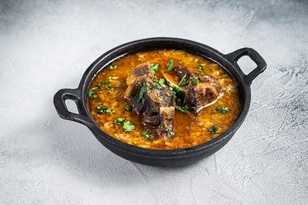 Суп харчо с говядиной, рисом, помидорами и специями на сковороде