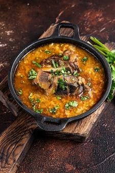 ラム肉、ご飯、トマト、にんじん、ピーマン、クルミ、スパイスが入ったハルチョースープ。暗い背景。上面図。