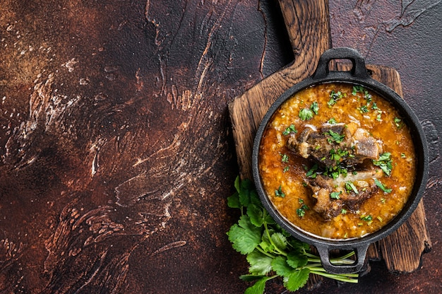 Суп харчо с бараниной, рисом, помидорами, морковью, перцем, грецкими орехами и специями. тьма