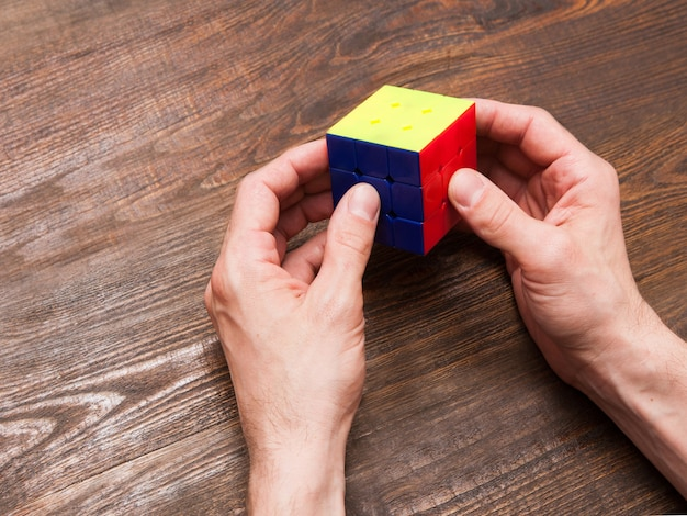 Kharkov, ukraine - april 6, 2017: man plays a cube of rubik on wooden background. intellectual game for smart people, popular logic colorful puzzle for increase creativity