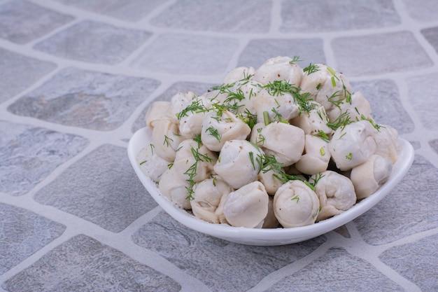 Pasta khinkali con ripieni ed erbe tritate in una ciotola bianca.