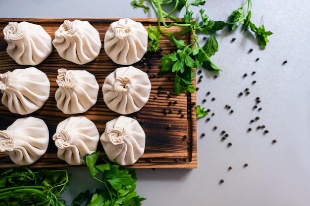 パセリと黒胡椒のエンドウ豆で飾られた木の板のヒンカリ餃子。
