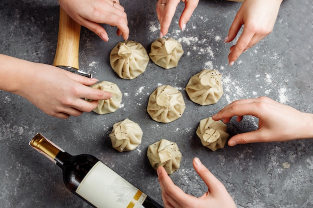 Khinkali, georgian dumplings, traditional georgian cuisine. hands of people take khinkali from the side. blue background, copy space.