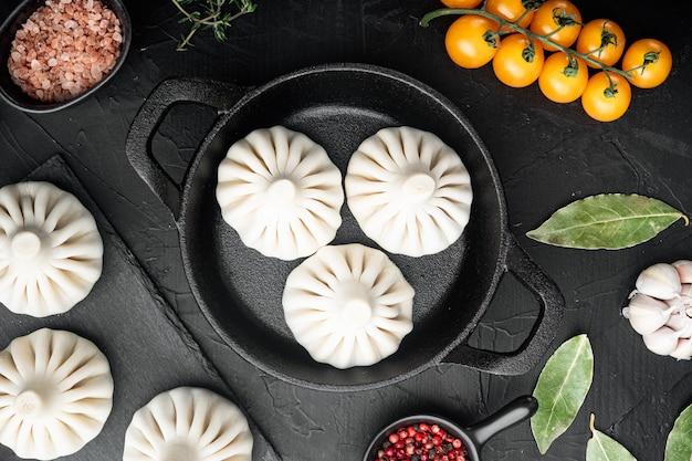 Хинкали, грузинские пельмени, набор традиционной грузинской кухни, на чугунной сковороде, на черном каменном столе, плоская планировка, вид сверху