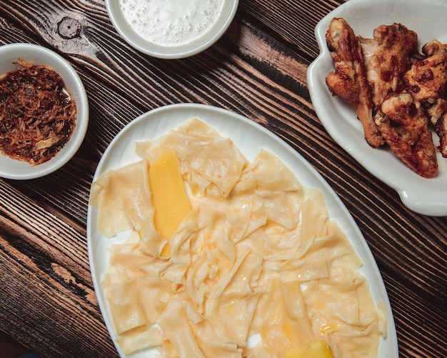 玉ねぎ炒めの葉の形のヒンカリ、および手羽先のソース