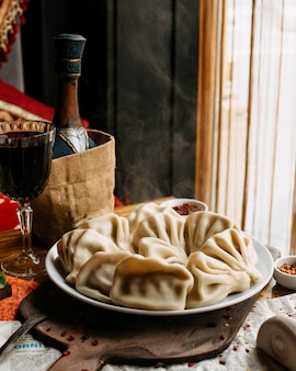 Khinkali sul piatto con un bicchiere di vino rosso