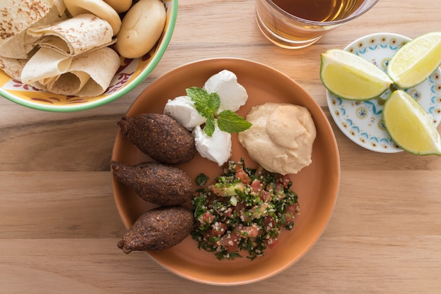Kibbeh (bulgur wheat/ meat ball), labneh, hummus and tabouleh and bowl with bread.