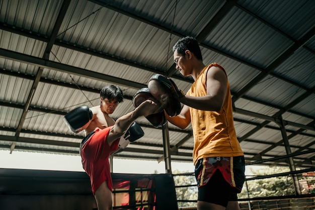 Kickboxer and coach training together with punching pads at boxing training camp