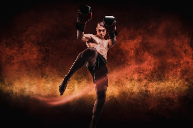 Kickboxer in a fiery arena. knee kick. mixed martial arts. sports concept.