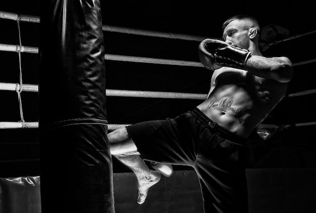 Кикбоксер бьет коленом по сумке. тренировка профессионального спортсмена. понятие мма, рестлинга, тайского бокса. смешанная техника