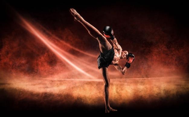 Кикбоксер на огненной арене. удар коленом. смешанные боевые искусства. спортивная концепция.