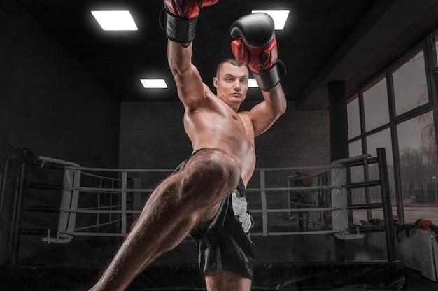 Кикбоксер в тренажерном зале. удар коленом. смешанные боевые искусства. спортивная концепция.