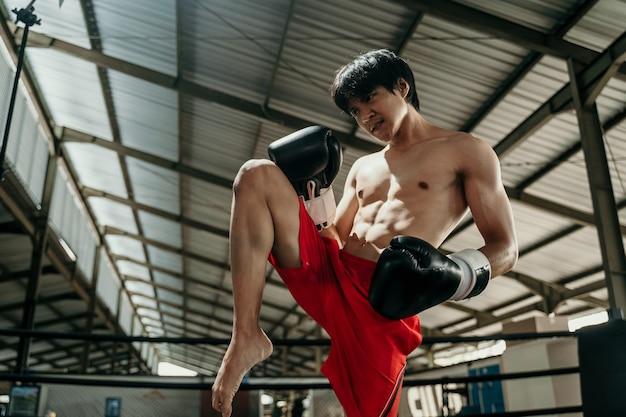 Copyspace와 반지에있는 kickboxer는 싸움이 무릎으로 스윙 움직임을 만들기 전에 뻗어 있습니다.