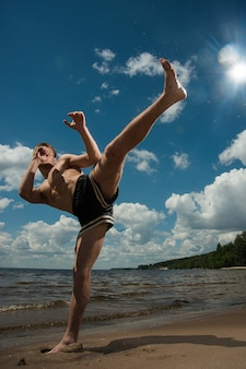 Kickboxer kicks in the open air in summer against the sea