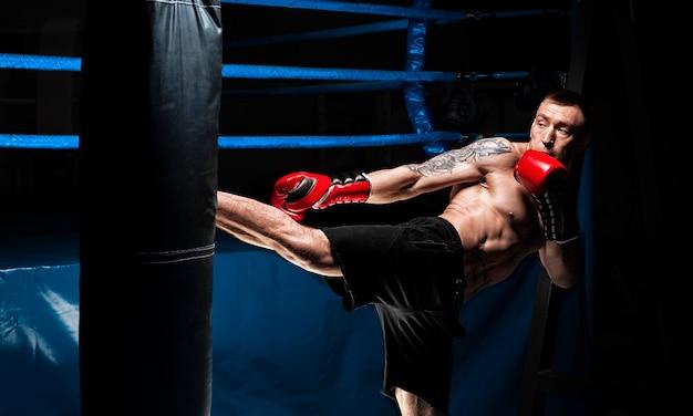 キックボクサーがバッグを蹴ります。プロスポーツ選手のトレーニング。総合格闘技、レスリング、ムエタイのコンセプト。ミクストメディア
