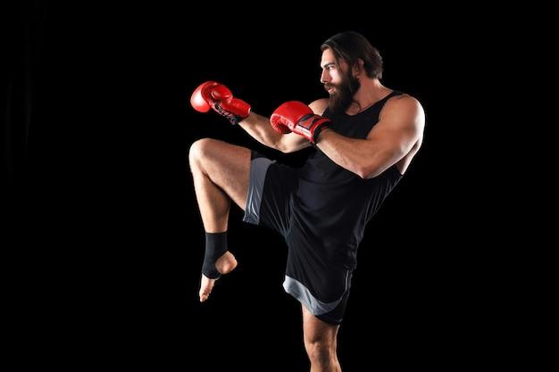 검은 배경에 맞서 싸우는 킥복서 남자. 스포츠 개념입니다.