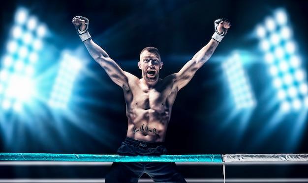 リングでポーズをとるキックボクサー。アスリートはロープを登り、スポットライトを背景に勝利を収めました。総合格闘技、レスリング、ムエタイのコンセプト。ミクストメディア