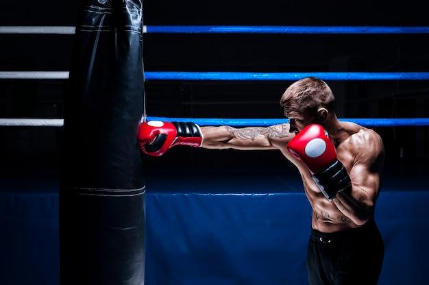 Кикбоксер пробивает мешок. тренировка профессионального спортсмена. понятие мма, рестлинга, тайского бокса. смешанная техника