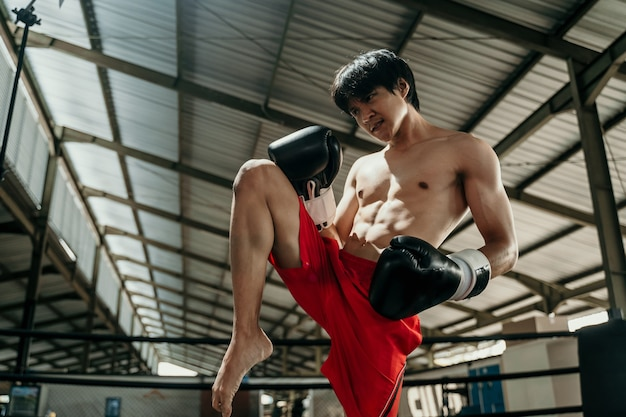 Kickboxer in the ring with the copyspace do stretches before the fight makes swing movements with his knee