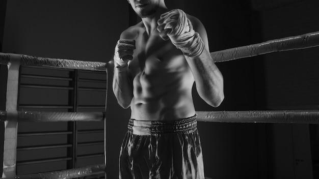 Кикбоксер стоит в углу ринга в атакующей стойке с перевязками на руках.