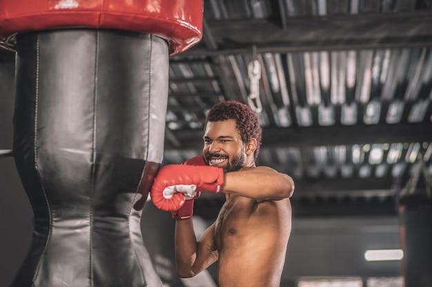 Кикбоксер. молодой темнокожий кикбоксер тренируется в тренажерном зале