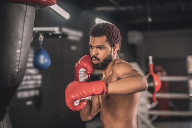 Kickboxer. young dark-skinned kickboxer having a workout in a gym